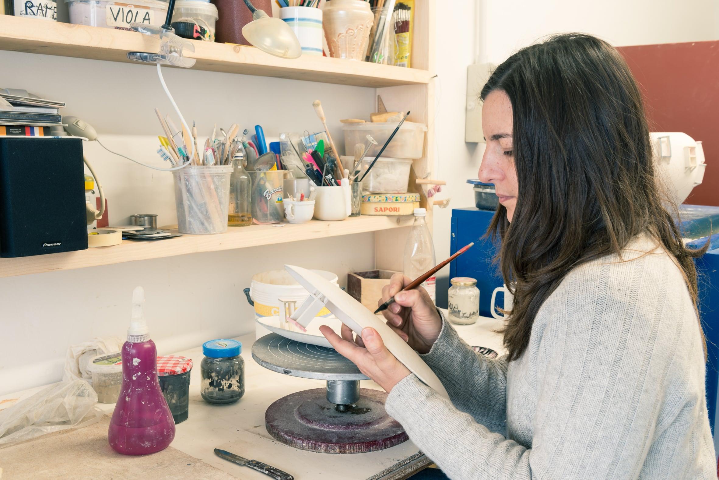 Elvira Keller durante la decorazione di un piatto in ceramica
