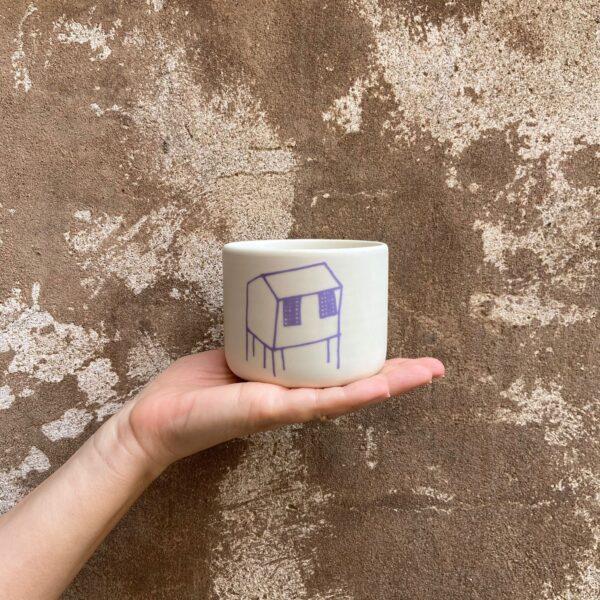 una tazza lilla della collezione palafitte tenuta sul palmo di una mano
